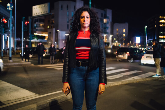 Mid adult woman with long curly hair on city street at night, portrait