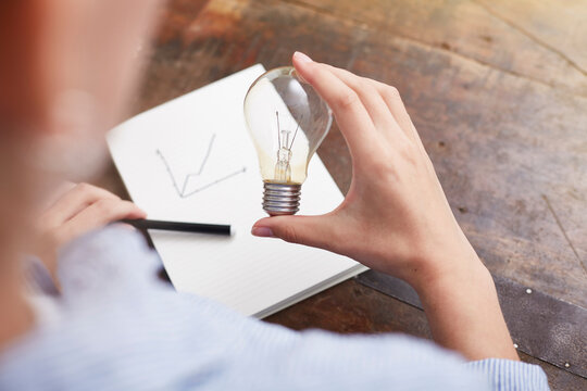 Woman with electric bulb planning way to save energy and money