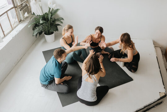 Friends making high five in yoga studio