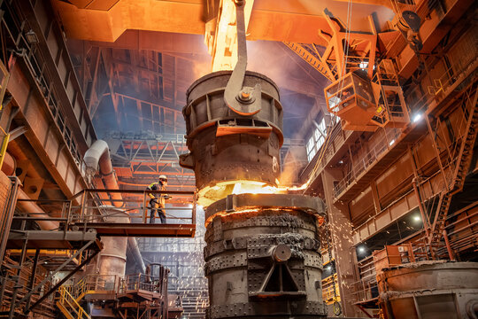 Steelworker starting molten steel pour in steelworks