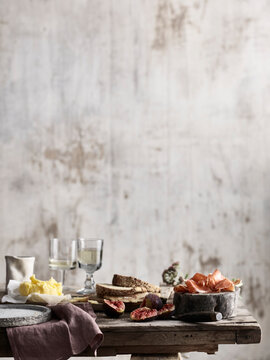 Spread of bread, butter, figs and ham on table