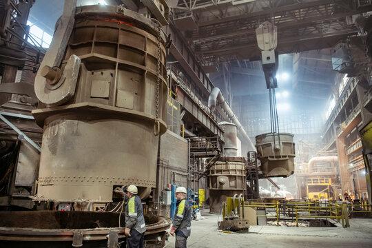 Workers preparing molten steel ladle in steelworks