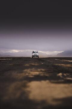 Off road vehicle on dirt track, black sky in background, Landmannalaugar, Iceland