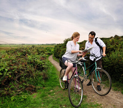 Mid adult cycling couple on rural dirt track looking at map, Southwold, Suffolk, UK