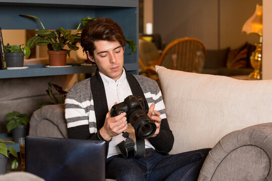 Man inspecting and learning to use camera in co-working space