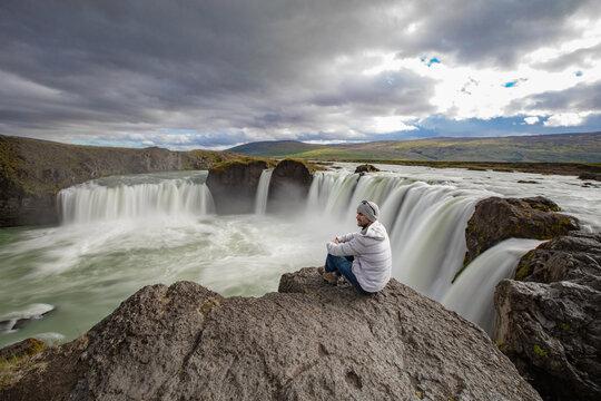 Man sitting on edge of rock, Godafoss waterfall, Bár_ardalur, Iceland