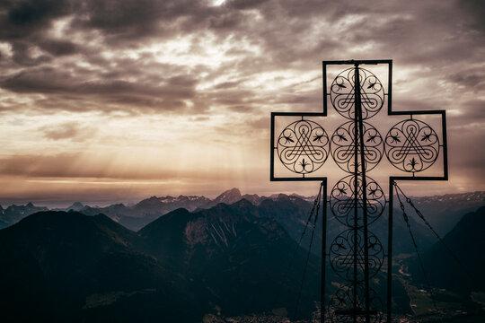 Large cross structure on peak, mountain ranges in background, Bludenz, Vorarlberg, Austria