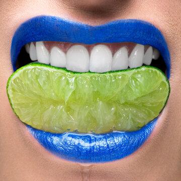 Blue lips biting on lime slice