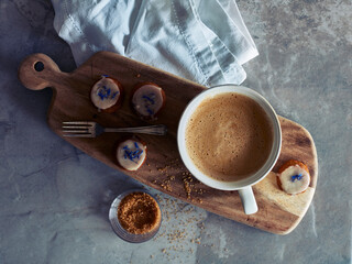 Cup of coffee and cookies on wooden board