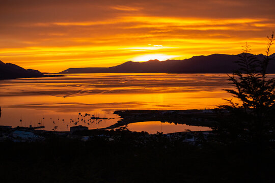 Sunset over the bay with mountains on the horizon.