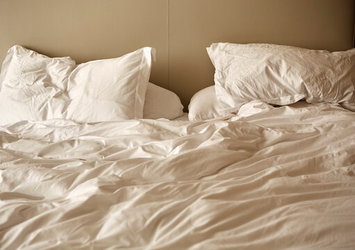 Unmade bed with crumpled duvet and pillows