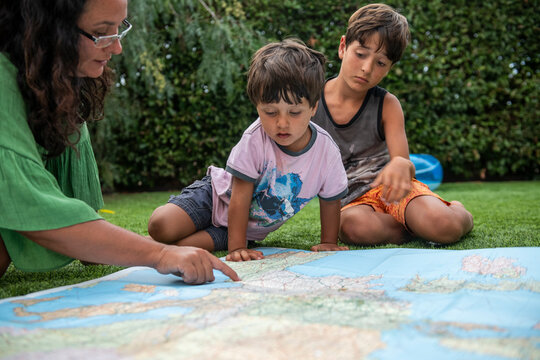 Woman and two boys sitting outdoors on a lawn, looking at a world map.