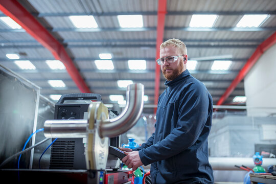 Engineer operating robotic arm welding machine in metal fabrication factory.