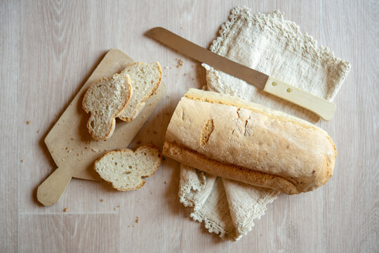 High angle close up of freshly baked white bread, bread knife, cutting board and linen napkin on wooden table.