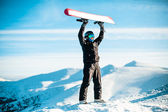 A person wearing a black ski suit, helmet and goggles on top of a mountain holding a red snowboard above their head.