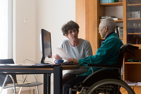 Senior woman sitting in a wheelchair at a computer, helper assisting with paperwork.