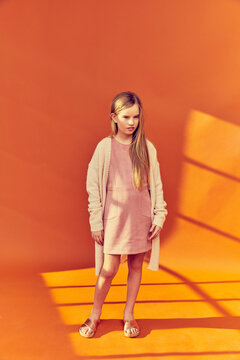 Portrait of girl with long blond hair wearing pink mini-dress and cream-coloured cardigan, on orange background.