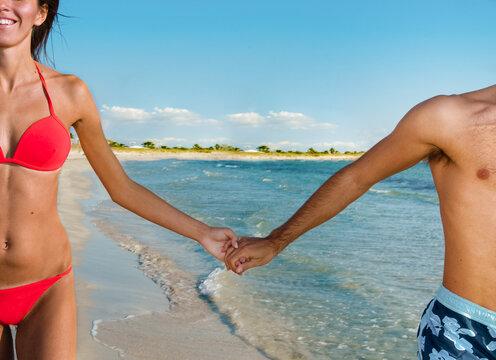 Man wearing swimming shorts and woman wearing red bikini walking hand in hand along sandy beach in Mediterranean.