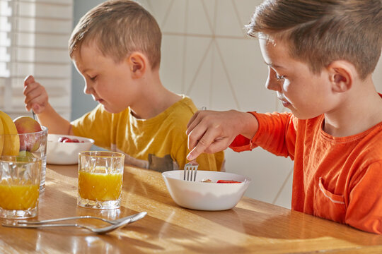 Two boys sitting at kitchen table, eating breakfast.