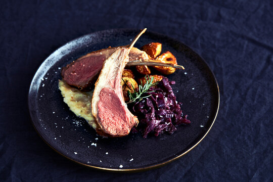 Plate of food with lamb chop, red cabbage and roast potatoes.