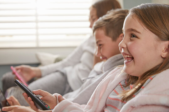 Group of children sitting on a sofa in their pajamas, watching television.