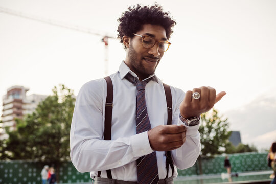Portrait of businessman wearing glasses, white shirt, brown tie and suspenders, adjusting his cuffs.