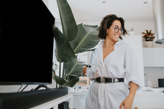 Smiling woman with brown hair wearing glasses standing in an apartment, watering plant.
