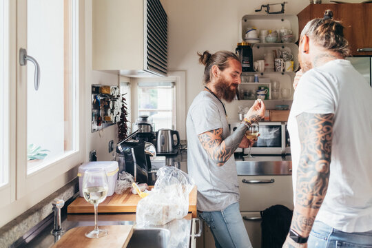Two bearded tattooed men with long brunette hair standing in a kitchen, eating.