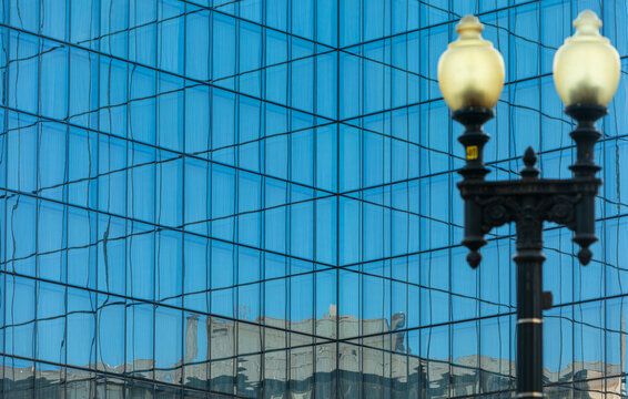 Washington, DC, USA - 05 April 2020: Modern blue Glass Facade of an Office Building, ancient Street Lamp blurred in Foreground