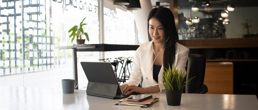 Horizontal photo of smiling businesswoman working with computer tablet and listen music on earphone.