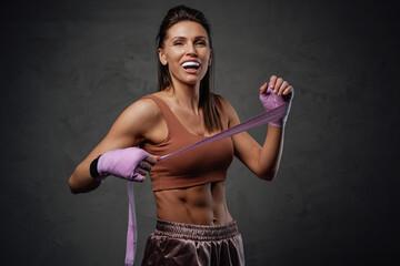 Joyful female boxer with bandages posing in studio