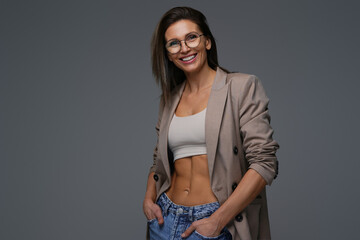 Smiling caucasian woman wearing jacket poses in gray background
