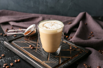 Glass of tasty latte on dark background
