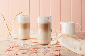 Glass cups of tasty latte on color background