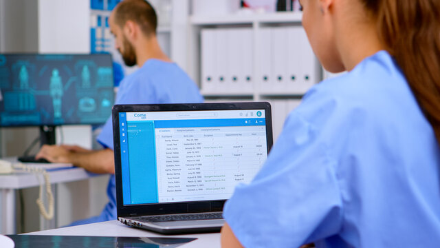 Professional doctor assistant checking medical records on laptop with x-ray and medical equipment around. Physician working in hospital clinic making appointments and analysing patient registration