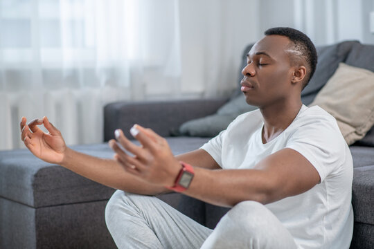 African american guy in white clothes meditating and looking peaceful