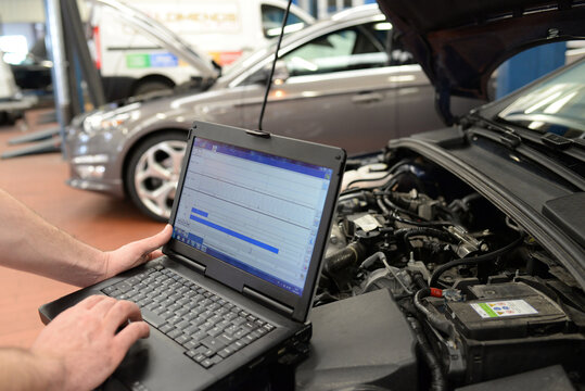 mechanic in a workshop checks and checks the electronics of the car - software update with a modern computer