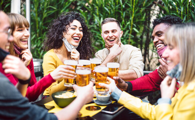 Fototapeta Young people toasting beer wearing open face mask - New normal life style concept with friends having fun together outside at brewery bar garden - Warm filter with focus on woman in yellow clothes