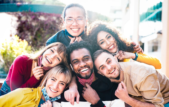 Multiracial people taking selfie with opened face mask outdoors - Happy life style concept with young students having fun together after lockdown reopening - Bright backlight sunshine filter