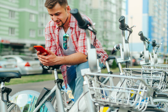 Positive man stands by the parking lot with a bicycle rental and uses a smartphone with a smile on his face. Tourist shares a bicycle for a walk on the Internet with a smartphone