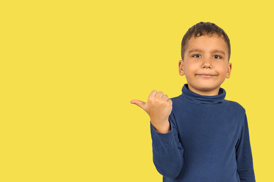 A boy of Asian appearance, preschool age, points with a finger to an empty space for your text on a yellow background.