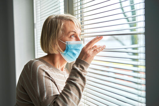 Senior woman in protective mask looking out the window at home