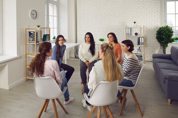 Obraz Young women telling their stories in therapy session or support group meeting. Female team talking, sharing news, discussing life situations, giving each other advice, working out solutions together - fototapety do salonu
