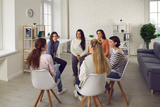 Young women telling their stories in therapy session or support group meeting. Female team talking, sharing news, discussing life situations, giving each other advice, working out solutions together