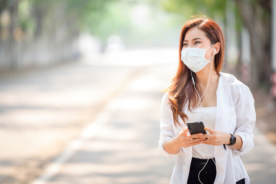 Young asian women Wearing a mask to prevent COVID-19 is using a smartphone on the street on a sunny hot summer day in the park.