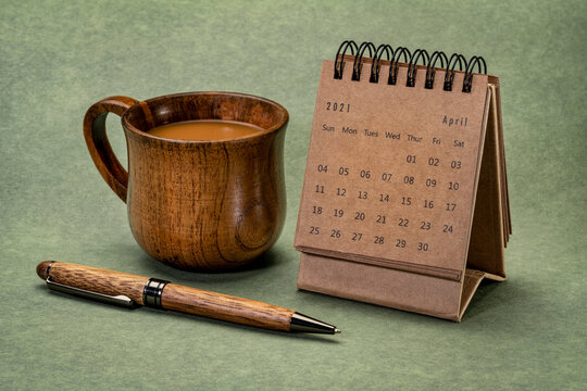 April 2021 - spiral desktop calendar against textured green paper with a cup of coffee and pen, time and business concept