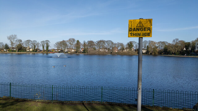 A moss covered yellow sing with black letters saying danger thin ice looking over the lake.