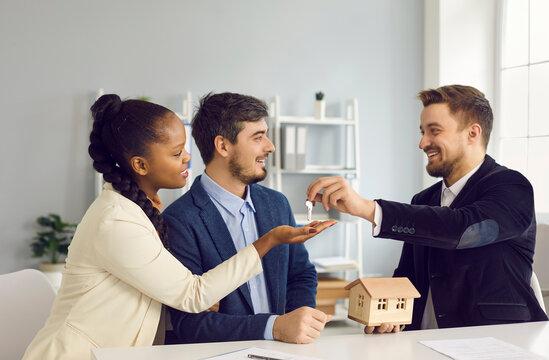 Property purchase and ownership concept. Millennial multiethnic couple taking key from new apartment buying first home together. Happy smiling realtor agent and interracial family buyers in office