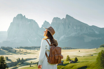 Fototapeta Happy young girl with white dress, hat and backpack in Alpe di Siusi, Dolomites.