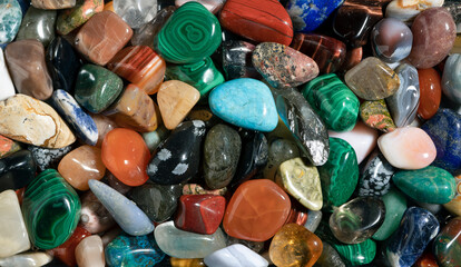 Gemstones background image. Various polished semi precious gemstones top view. Chakra healing stones and crystals. Turquoise, amethyst, quartz, agate and many more.